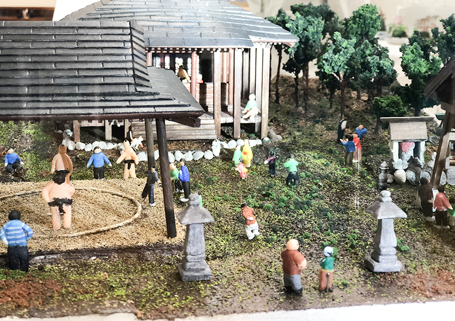 昭和中期頃、多くの人々で賑わったとされる「旧暦8月8日 大日如来堂 例大祭での相撲大会」と設定し、管理者から得た情報を参考に、境内の様子を細かなディティールとして立ち上がるように制作したジオラマ