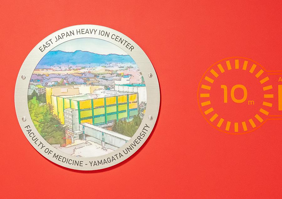 東日本重粒子センター。シャトル内部からの景色を想定した円形の窓の絵には、重粒子センターの10メートル上空から眺めた風景が描かれている。