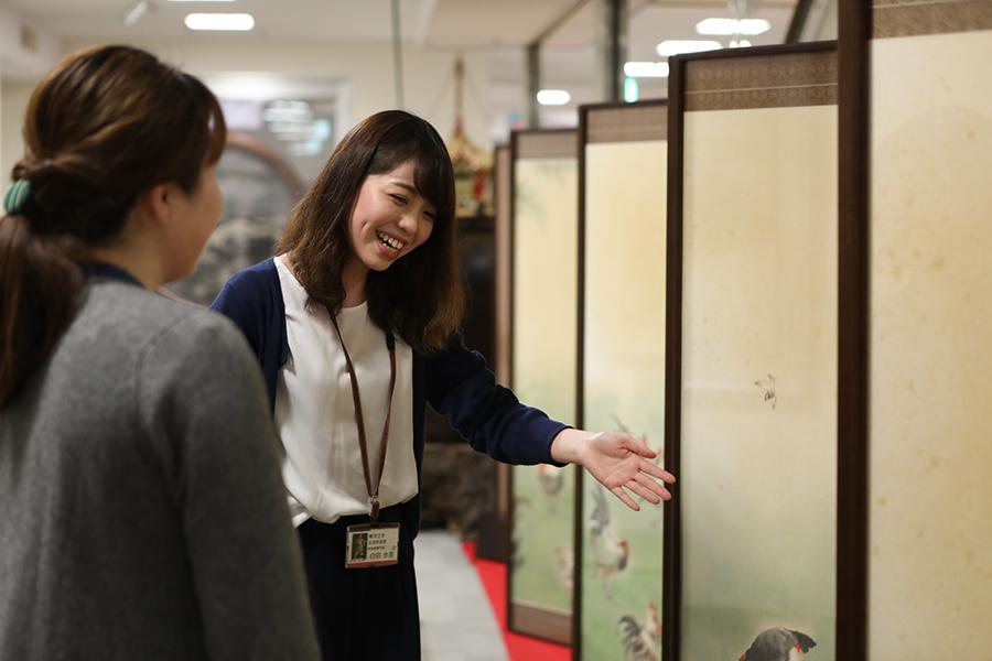 寒河江市美術館 美術館専門員 白田歩香さん 来館者に作品の説明を行う様子