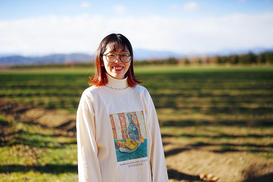 酪農アーティスト、版画家 下山明花さん 広大な牧草地を背景に